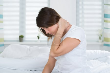 Photo for Young Woman Suffering From Neck Pain Sitting On Bed - Royalty Free Image