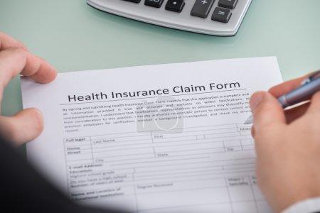 Photo pour Gros plan du mâle remplissage formulaire de réclamation d'assurance maladie - image libre de droit