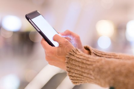 Photo for Woman using mobile phone with blank screen at shopping center - Royalty Free Image