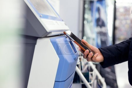 Woman paying on ticketing machine by cell phone