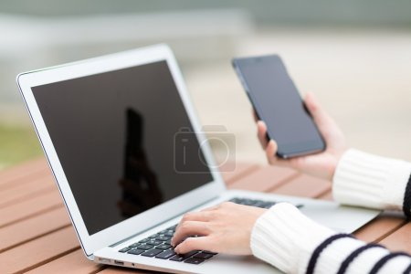 Woman using laptop and cellphone