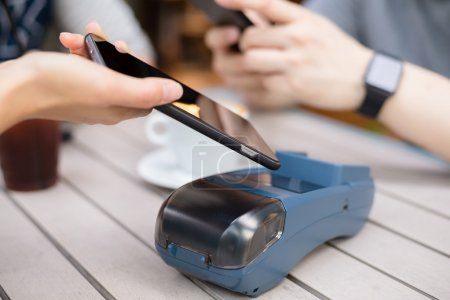 Woman using cellphone for paying the bill