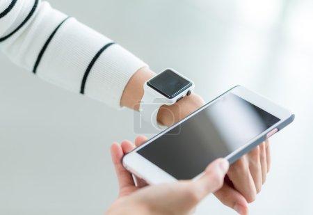 Photo pour Image recadrée de femme connectant montre intelligente et téléphone portable - image libre de droit