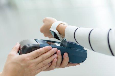 Photo pour Femme utilisant la montre intelligente pour payer la facture avec la technologie NFC - image libre de droit