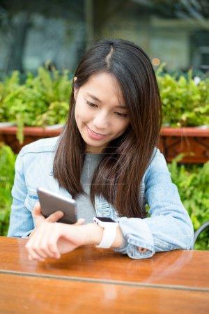 Photo pour Asiatique jeune femme à l'aide de téléphone cellulaire et montre intelligente au café extérieur - image libre de droit