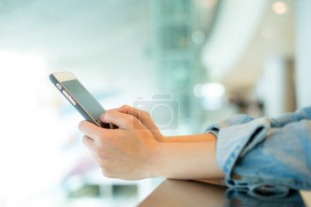 Photo for Close up of woman using mobile phone at shopping mall - Royalty Free Image