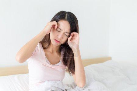 Photo pour Asiatique jeune femme souffrant de maux de tête et se reposant sur le lit - image libre de droit
