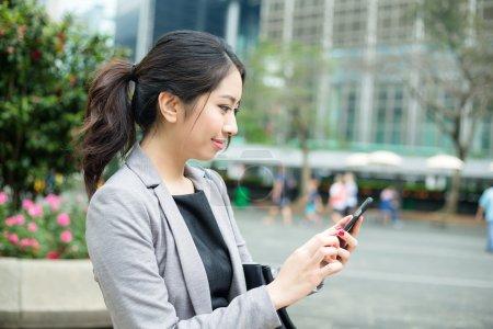 Photo pour Jeune femme d'affaires asiatique en costume d'affaires en utilisant un téléphone portable à l'extérieur - image libre de droit