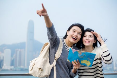 women tourists looking for destination on map