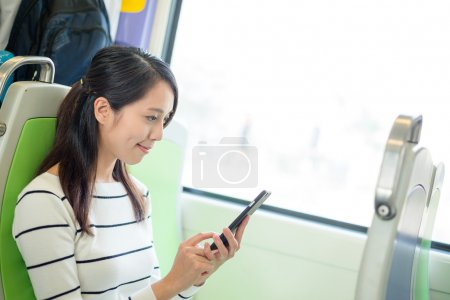 woman using cellphone inside train