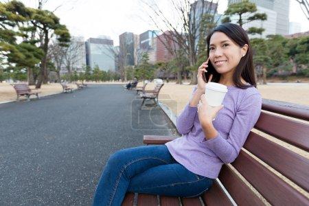 Photo pour Asiatique jeune femme avec tasse de café parler sur téléphone portable au parc - image libre de droit