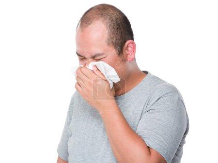 Asian man sneeze on tissue