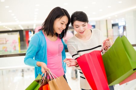 Photo pour Deux jeunes femmes asiatiques avec des sacs à provisions dans le centre commercial - image libre de droit