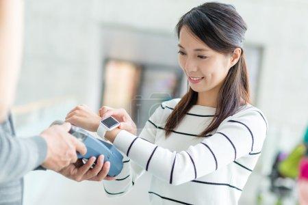 Photo pour Asiatique jeune femme en utilisant montre intelligente pour payer sur pos terminal - image libre de droit