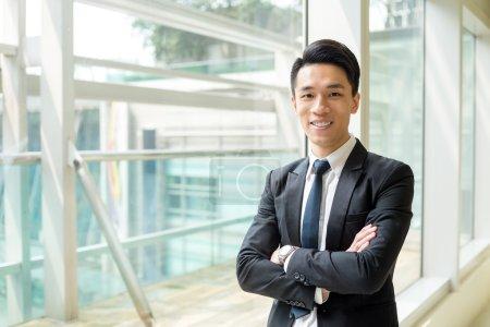 Photo pour Jeune homme d'affaires asiatique en costume d'affaires permanent au bureau avec les bras croisés - image libre de droit