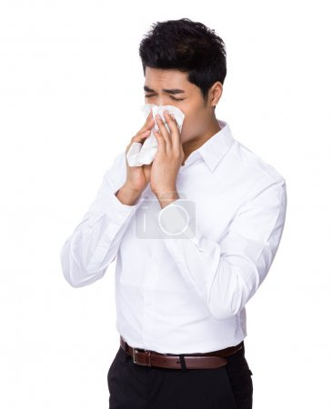 Young businessman sneezing