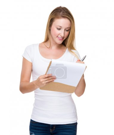 Photo for Caucasian young blond woman writes on clipboard - Royalty Free Image