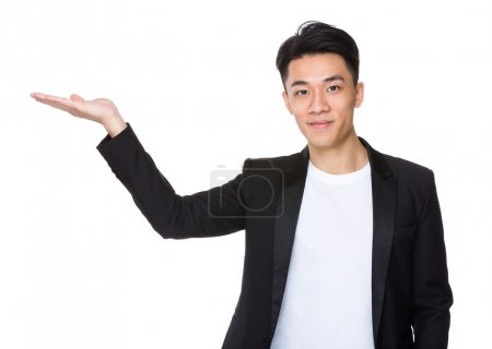 Photo for Asian handsome man in black jacket with hand presentation - Royalty Free Image