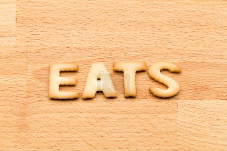 Word eats biscuit over the wooden background