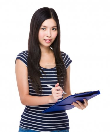 Young asian woman write on clipboard