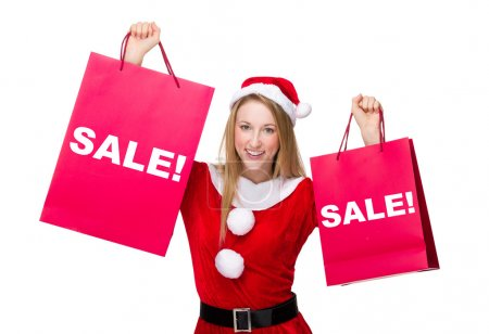 Photo for Woman in christmas costume with shopping bags showing a word sale - Royalty Free Image
