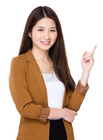 Photo pour Asiatique jeune femme d'affaires en costume d'affaires avec doigt vers le haut - image libre de droit