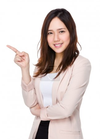 Photo pour Jeune femme asiatique en costume d'affaires avec le doigt pointer vers le haut - image libre de droit