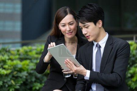 Photo pour Deux personnes d'affaires asiatiques à l'aide de la tablette numérique ensemble à l'extérieur - image libre de droit