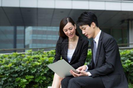 Photo pour Deux personnes d'affaires asiatiques travaillent ensemble à l'extérieur en sur ordinateur portable - image libre de droit