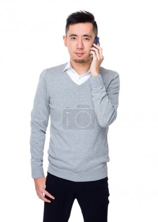 Photo for Young asian businessman in grey sweater talk to cellphone - Royalty Free Image