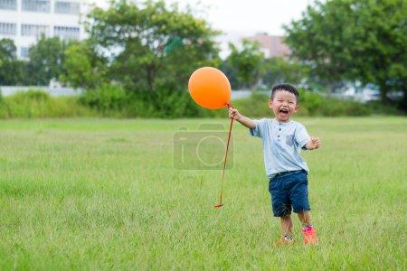 Photo pour Mignon asiatique petit garçon avec l 'orange ballon à parc - image libre de droit