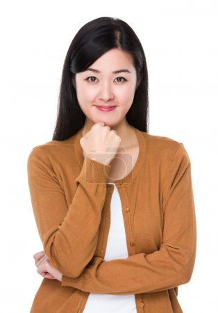 Photo for Asian young woman in brown cardigan with hand on chin - Royalty Free Image