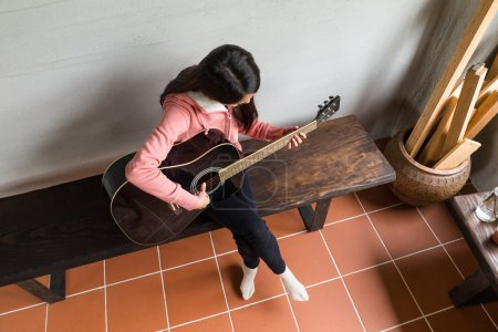 woman playing on acoustic guitar