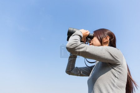woman looking through binoculars at outdoors