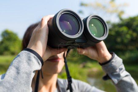 woman looking through binoculars at outdoors
