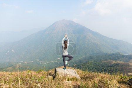 Photo pour Asiatique jeune femme faire du yoga au sommet de la montagne - image libre de droit