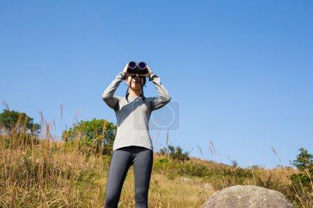 Woman looking though the binocular