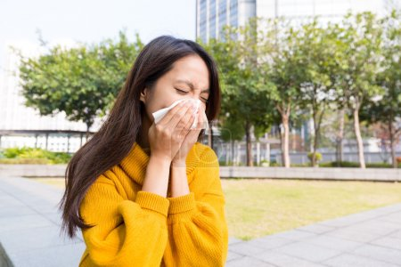 Asian woman blowing nose