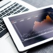 Stock market graphs on tablet pc with laptop compu...