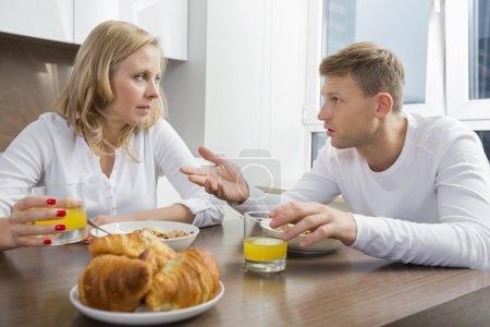 Photo pour Couple adulte moyen parlant tout en prenant le petit déjeuner à la maison - image libre de droit