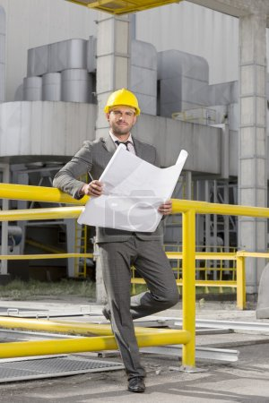 Photo for Young male architect holding  blueprint outside industry - Royalty Free Image