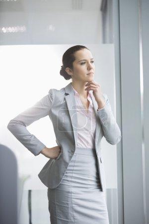 Photo pour Réfléchie jeune femme d'affaires permanent au bureau - image libre de droit