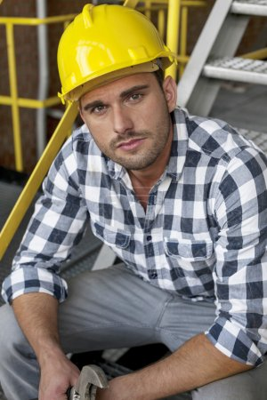 Worker with wrench sitting on steps