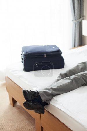 Man lying on bed in hotel room