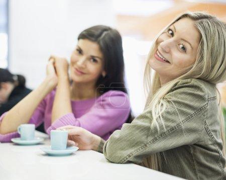 Empresarias sonriendo en la mesa de la cafetería