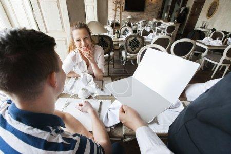 Waiter showing menu to couple