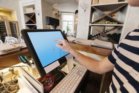 Cashier touching computer screen