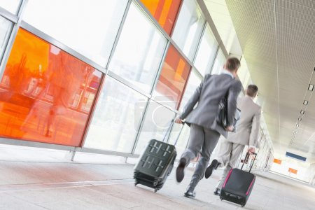 businessmen with luggage rushing