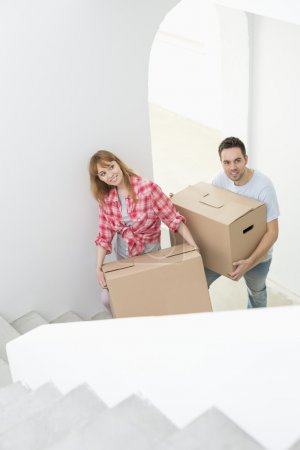 Couple carrying boxes up stairs