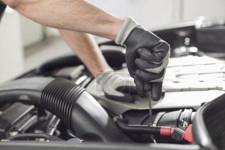 Photo pour Image recadrée de mécanicien automobile réparation de voiture en magasin automobile - image libre de droit